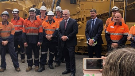 Scott Morrison in the Hunter on Tuesday, posing for a photo with workers in neon orange high-vis gear.