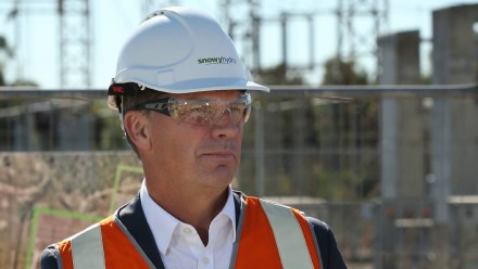 A photograph of Energy and Emissions Reduction Minister Angus Taylor, wearing a hard hat and orange reflective gear at a coal-fired power station.