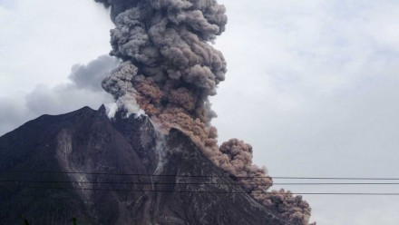 A photograph of Mount Sinabung volcano in Indonesia, with smoke billowing out of the top.