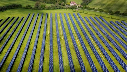 An aerial photograph of a large green grass field covered in solar panels.