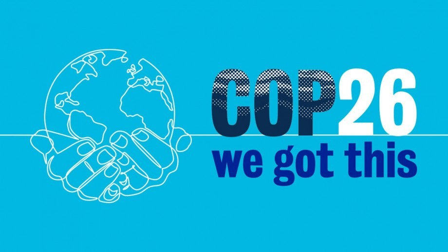 A light blue background, with a white drawing of hands holding the globe, with bold letters spelling out 'COP26 - We Got This' on the side.