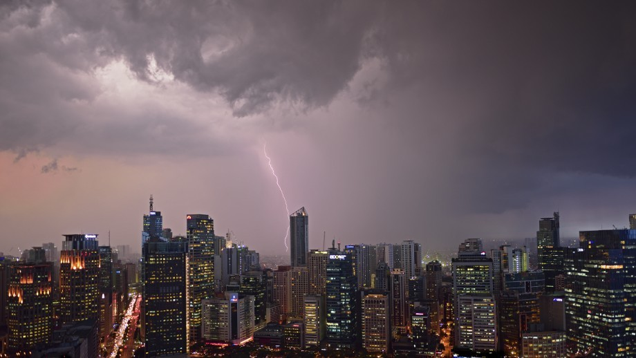 A photography of a city, with dark grey and purple stormclouds filling the sky, and a stroke of lighting coming down from the clouds.