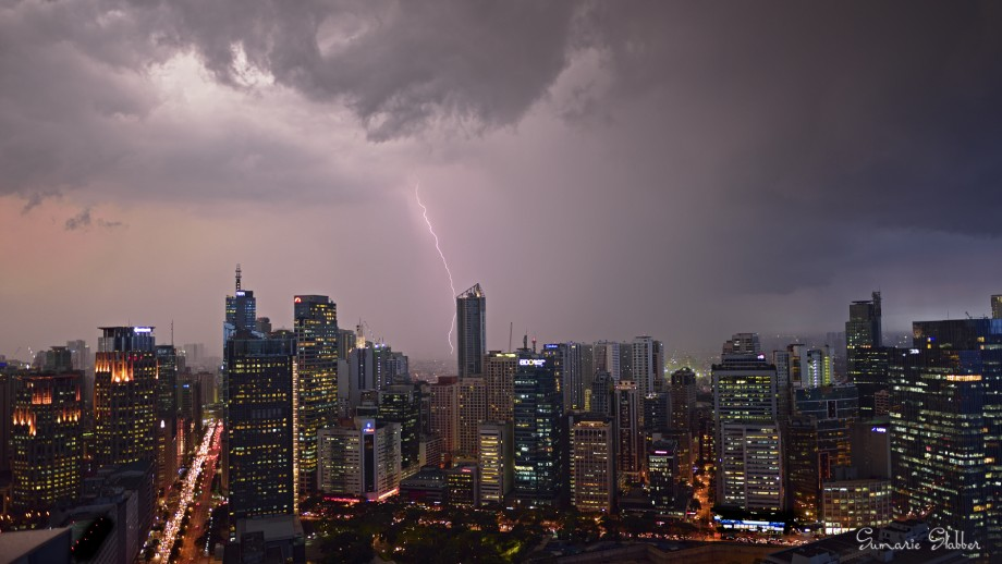 A photograph of a storm over a city, with a lightening bolt striking one of the sky-scrapers.
