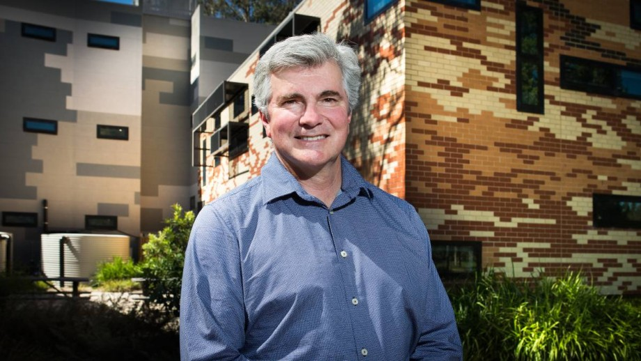 Prof Mark Howden standing in front of the Frank Fenner building at the Australian National University,