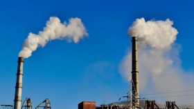 A photograph of chimneys at a coal fired power station, with a clear blue sky behind.