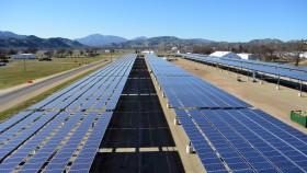 A photograph of solar panels running alongside a road.