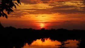 A photograph of the sun setting over a lake, with the sky all a deep orange colour.