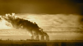 A photograph of a coal-fired power station in the distance, with the sun shining from behind, and smoke billowing out of the chimneys.
